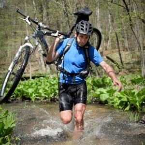cyclist Mark Vantongergen running through river with bike