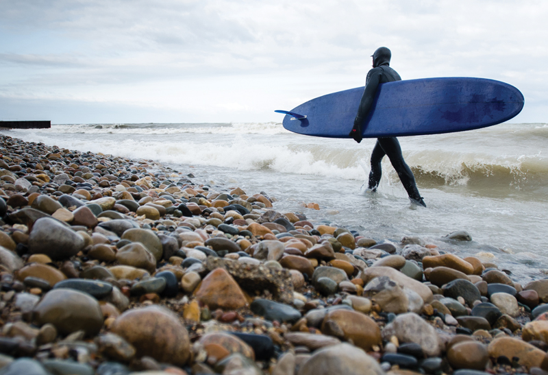 Surfer staying warm in advanced wetsuit technology on Lake Huron.