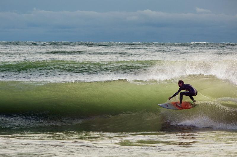 Surfer rides a curl on Lake Michigan