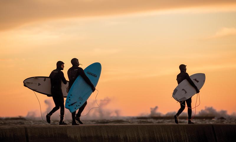 Surfers head out along a Lake Michigan pier