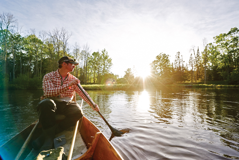 Josh Greenberg paddles an Au Sable riverboat