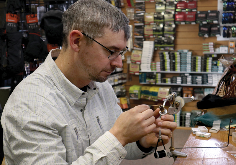 Greenberg ties flies in his fly shop.