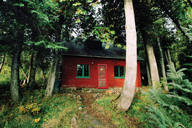 Our little red cabin nestled in the woods — home away from home. Signs mark an adventure through the woods, below.