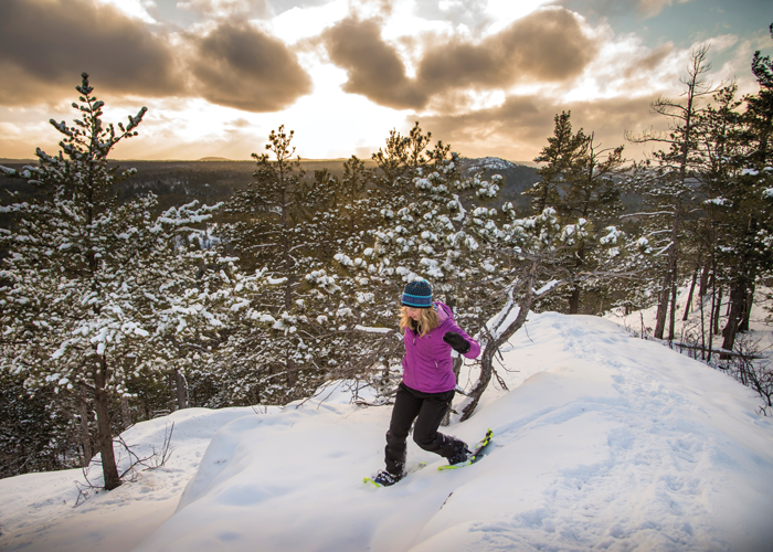 A snowshoe hiker visits a scenic overlook at Sugarloaf Mountain in Marquette