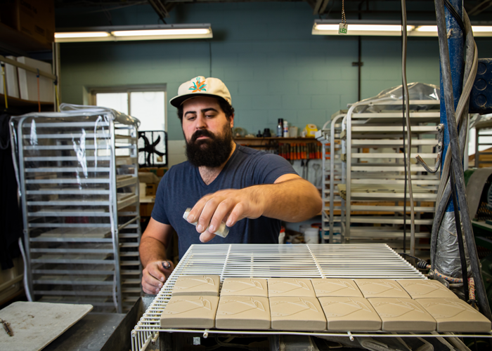 Mitch Segall is part of the pressing department where unfired clay is pressed into shape, edged and trimmed before drying.