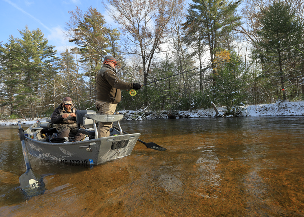 Pere Marquette River Lodge owner and guide Frank Willetts, left, sits and ties a fly on a line as his client Shane Hensley fishes.